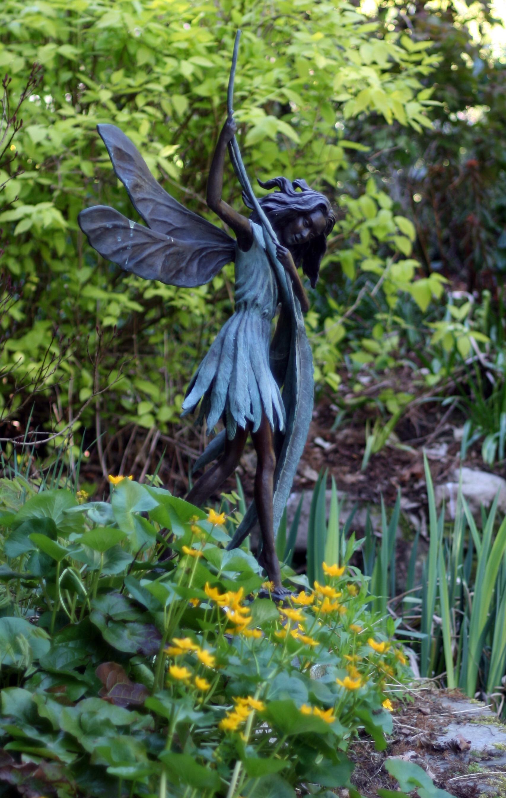 #Acessibilidade Foto de uma escultura em bronze de uma fada em um jardim