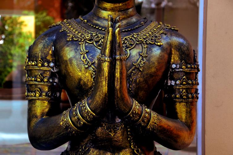 Fotografia de uma estátua de Buda Tibetano com as mãos em prece
